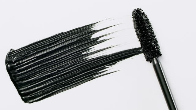 close up and slow motion of a black mascara swoosh created by a mascara wand on white background - mascara stock videos & royalty-free footage