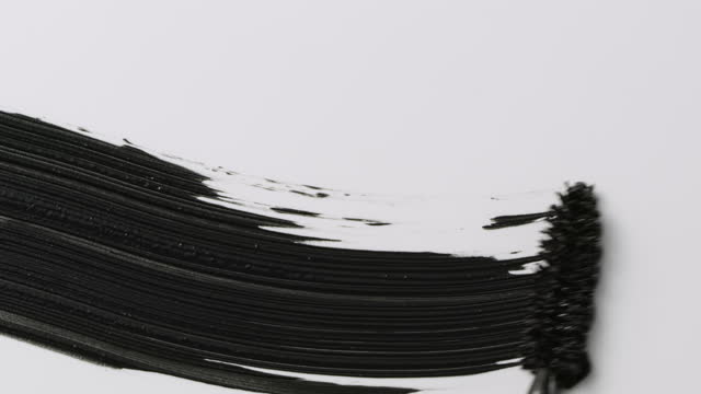 close up and slow motion of a black mascara swoosh created by a mascara wand on white background - kalligraphieren stock-videos und b-roll-filmmaterial