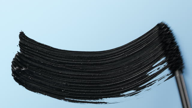 close up and slow motion of a black mascara swoosh created by a mascara wand on light blue background - blue background stock videos & royalty-free footage