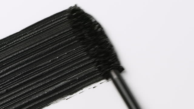 close up and slow motion of a black mascara swoosh created by a mascara wand on white background - art and craft stock videos & royalty-free footage