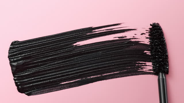close up and slow motion of a black mascara swoosh created by a mascara wand on light pink background - mascara stock videos & royalty-free footage