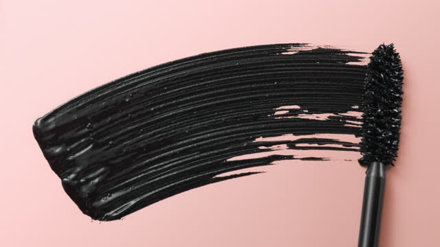 close up and slow motion of a black mascara swoosh created by a mascara wand on light pink background - メイクアップブラシ点の映像素材/bロール