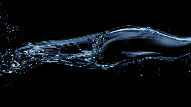 close up and slow motion of an clear blue water stream flowing, colliding and splashing in air against a black background - flowing stock videos & royalty-free footage