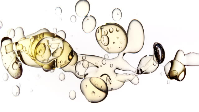 close up and slow motion of clear gold liquid pouring into water from right side transforming into various sized bubbles floating on white background - stationary stock videos & royalty-free footage