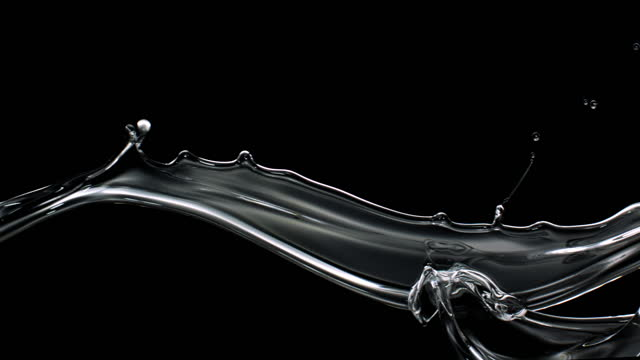 close up and slow motion of clear oil water stream flowing, colliding and splashing in air against a black background - flowing stock videos & royalty-free footage
