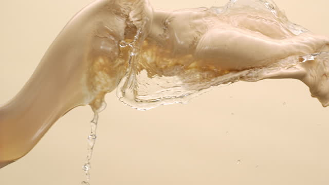 close up and slow motion of cream foundation colored liquid and water colliding and throwing in air with splash against a beige background - beige stock videos & royalty-free footage