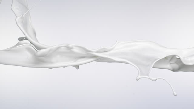 close up and slow motion of liquid milk flowing and throwing in air with splash against a white background - beige stock videos & royalty-free footage