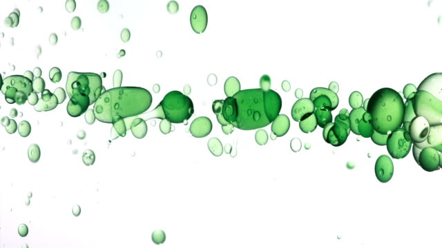 close up and slow motion of pouring green hued oil from right and creating a row of bubbles under water while bouncing around on white background - liquid stock videos & royalty-free footage