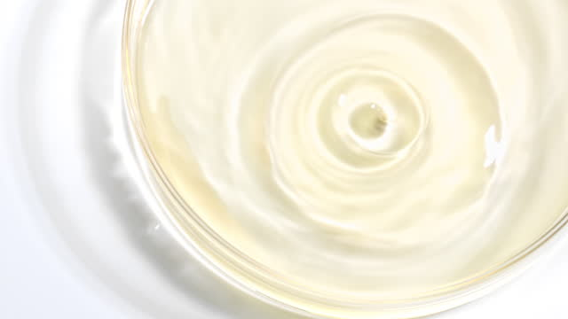 close up and super slow motion of gold colored water ripples on a petri dish with reflection on a white surface - glass material stock videos & royalty-free footage