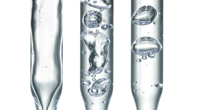 close up and super slow movement of clear water bubbling by pouring water inside three clear pipettes in a row on white background - curiosity stock videos & royalty-free footage