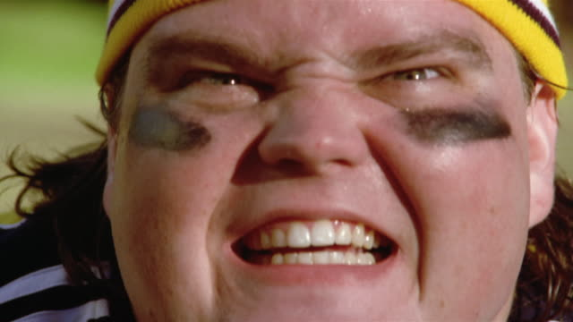 Close up angry football player wearing knit cap and eyeblack scowling and snarling