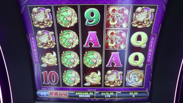 Close up animation of symbolic chinese animal and alphanumeric characters randomly rotate on a screen at a slot machine at the Global Gaming Expo...