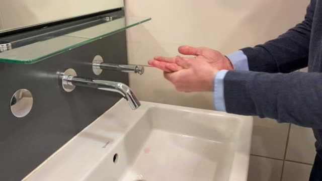 close up anonymous shot of man washing hands in relation to coronavirus - cleaning stock videos & royalty-free footage