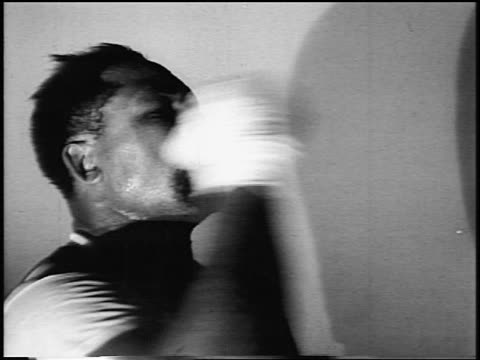 B/W 1956 close up Archie Moore punching speed bag in training in gym / newsreel