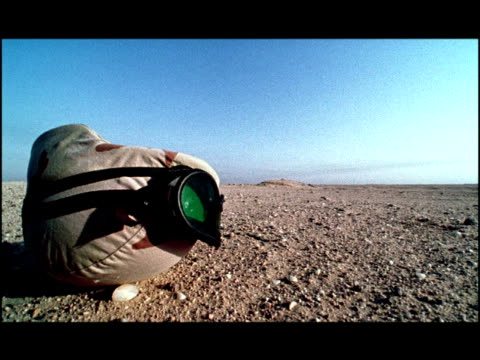 close up army helmet and goggles sitting on barren desert ground/ kuwait - army helmet stock videos & royalty-free footage