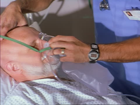 close up as a male nurse in scrubs places an oxygen mask on the face on an ill elderly patient