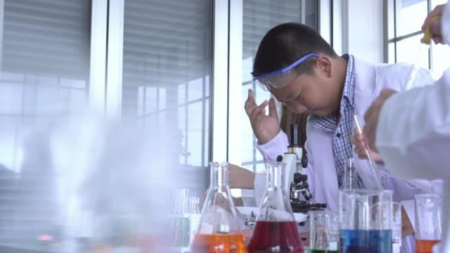 vídeos de stock, filmes e b-roll de feche acima do menino de ásia faça o teste de laboratório com espaço da cópia - inventor