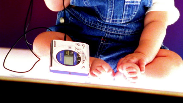 high contrast close up asian baby in wearing headphones in studio / tilt down to walkman by feet - 携帯オーディオプレーヤー点の映像素材/bロール