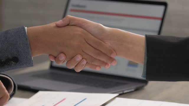 vídeos de stock, filmes e b-roll de feche o aperto de mão do empresário asiático após cumprir plano de marketing e terminar reunião no escritório - conformidade
