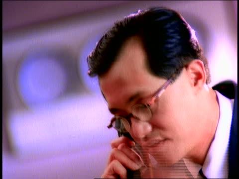 vídeos de stock, filmes e b-roll de canted close up asian businessman on phone removing eyeglasses / rack focus world time-zone clocks on wall - vestuário de trabalho formal