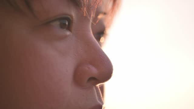 アジアの中国の中年女性の目を閉じて、朝のホームワークアウトの後、屋外のバックライト付きの日差しを見て目をそらす - 横顔点の映像素材/bロール