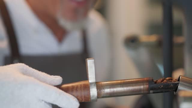 コーヒーロースター焙煎生コーヒー豆の匂いをチェックから抽出するトリーアを保持しているアジアの中国人上級職人を閉じる - 人間の鼻点の映像素材/bロール