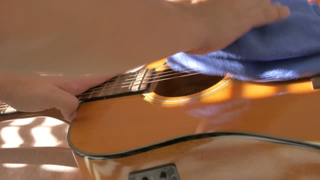 close up asian man hand clean guitar on bed, concept day in the life fever covid-19 quarantine - day in the life stock videos & royalty-free footage
