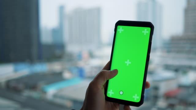 nahaufnahme asian man hält einen leeren green screen smart-gerät, mit android phone. bangkok stadt. - vorlage stock-videos und b-roll-filmmaterial