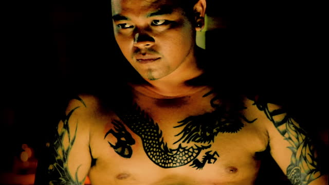 Close up Asian man w/dragon tattoos on chest looking at CAM