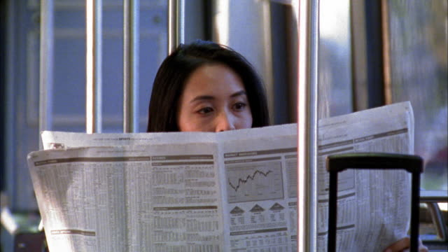 stockvideo's en b-roll-footage met close up asian woman reading financial pages of ewspaper on train or bus - krant