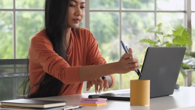 close up asian woman rearrange stuff on desk and closed laptop when finish working at home - arranging stock videos & royalty-free footage