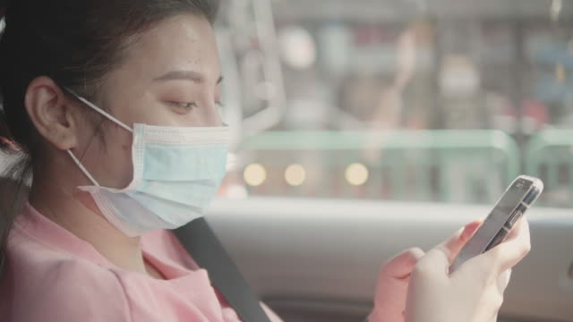 close up : asian woman wear face mask using smartphone touchscreen sitting in the car. - passenger stock videos & royalty-free footage