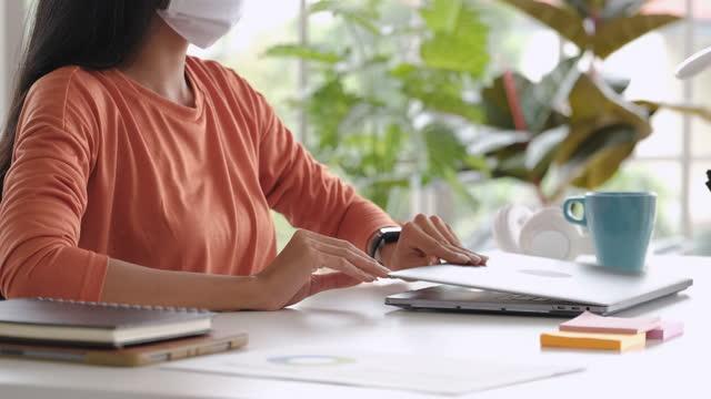 vídeos de stock, filmes e b-roll de close-se mulher asiática usar máscara e reorganizar coisas em mesa e laptop fechado quando terminar de trabalhar em casa - o fim