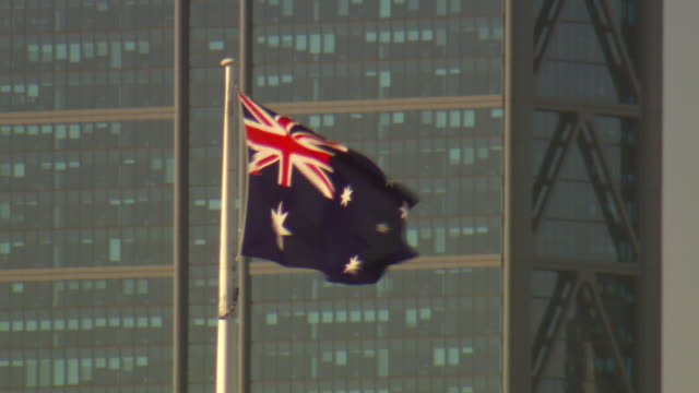 Close up Australian flag flying mirrored city office building in the background