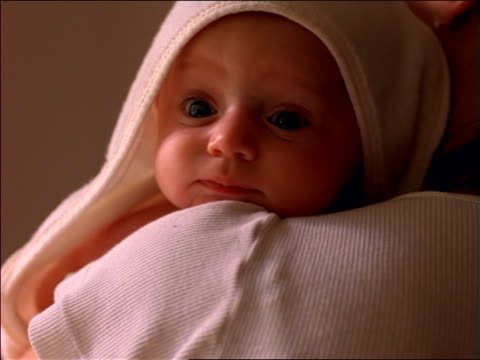 close up baby girl on shoulder of mother with towel on head looking at camera - burping stock videos & royalty-free footage