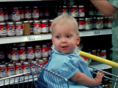 1960 close up baby girl sitting in shopping cart / woman putting jars of baby food in cart in store - consumerism stock videos and b-roll footage