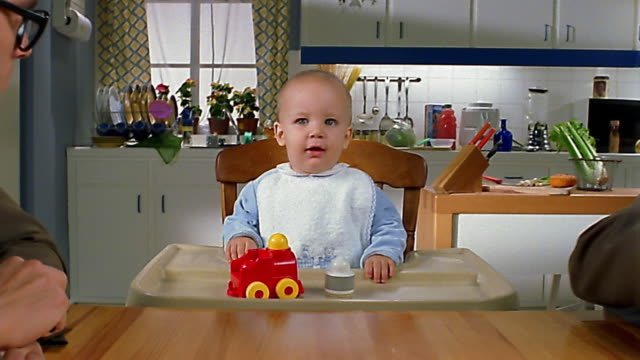 Close up baby in high chair / zoom out to medium shot businessmen offering contracts to baby