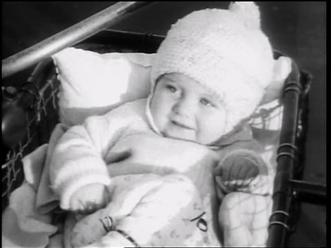 B/W 1931 close up baby in knit cap waving in baby carriage / Chicago / newsreel