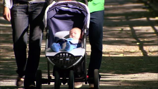 vídeos y material grabado en eventos de stock de close up baby in stroller / tilt up woman and man walking and pushing stroller - cochecito para niños