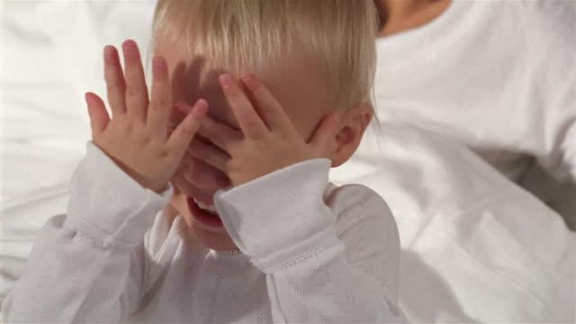 vídeos de stock e filmes b-roll de close up baby playing peek-a-boo / mother behind him in bed smiling - atrás