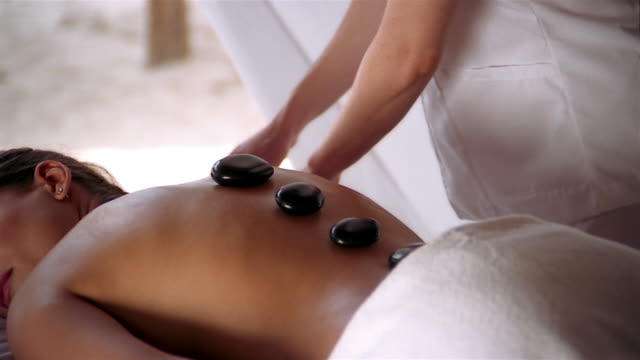 close up back of a woman receiving hot stone massage from masseuse - tropical climate stock videos & royalty-free footage