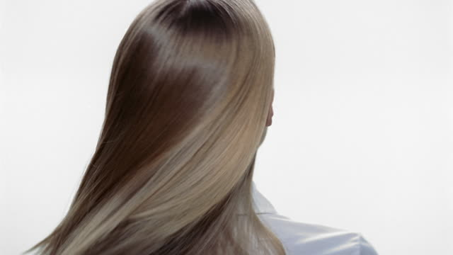 Close up back of the head of woman with long hair / shaking head back and forth