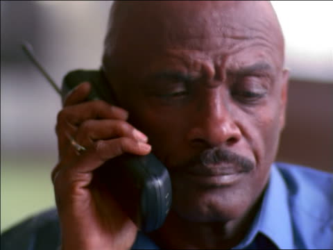 close up bald Black man talking on cellular phone + looking off screen