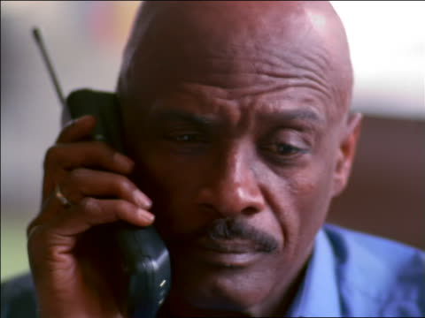 close up bald black man talking on cordless phone - einzelner mann über 40 stock-videos und b-roll-filmmaterial