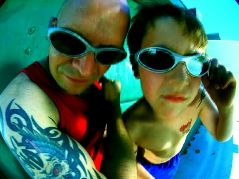 close up bald man and boy posing with tattoos on arms + sunglasses / mexico city - fischaugen objektiv stock-videos und b-roll-filmmaterial