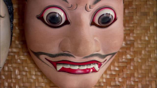 Close up Balinese mask with bulging eyes and fanged teeth / Ubud, Bali, Indonesia