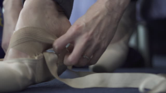 close up ballerina putting on pointe ballet shoes and tying ribbons up - ballet dancing stock videos & royalty-free footage