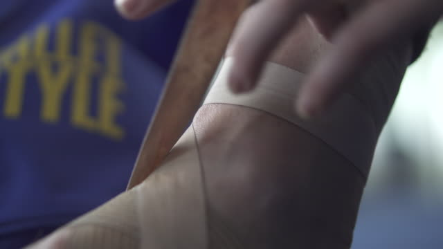 close up ballerina trying ribbon of ballet shoes around her ankle - ballet shoe stock videos & royalty-free footage
