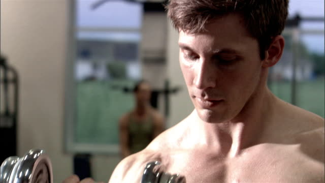 close up bare chest of young man lifting weights in health club/ pan up to man's face - pectoral muscle stock videos and b-roll footage