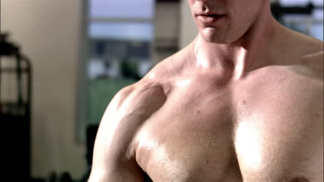 Close up bare chest of young man lifting weights in health club/ pan up to face
